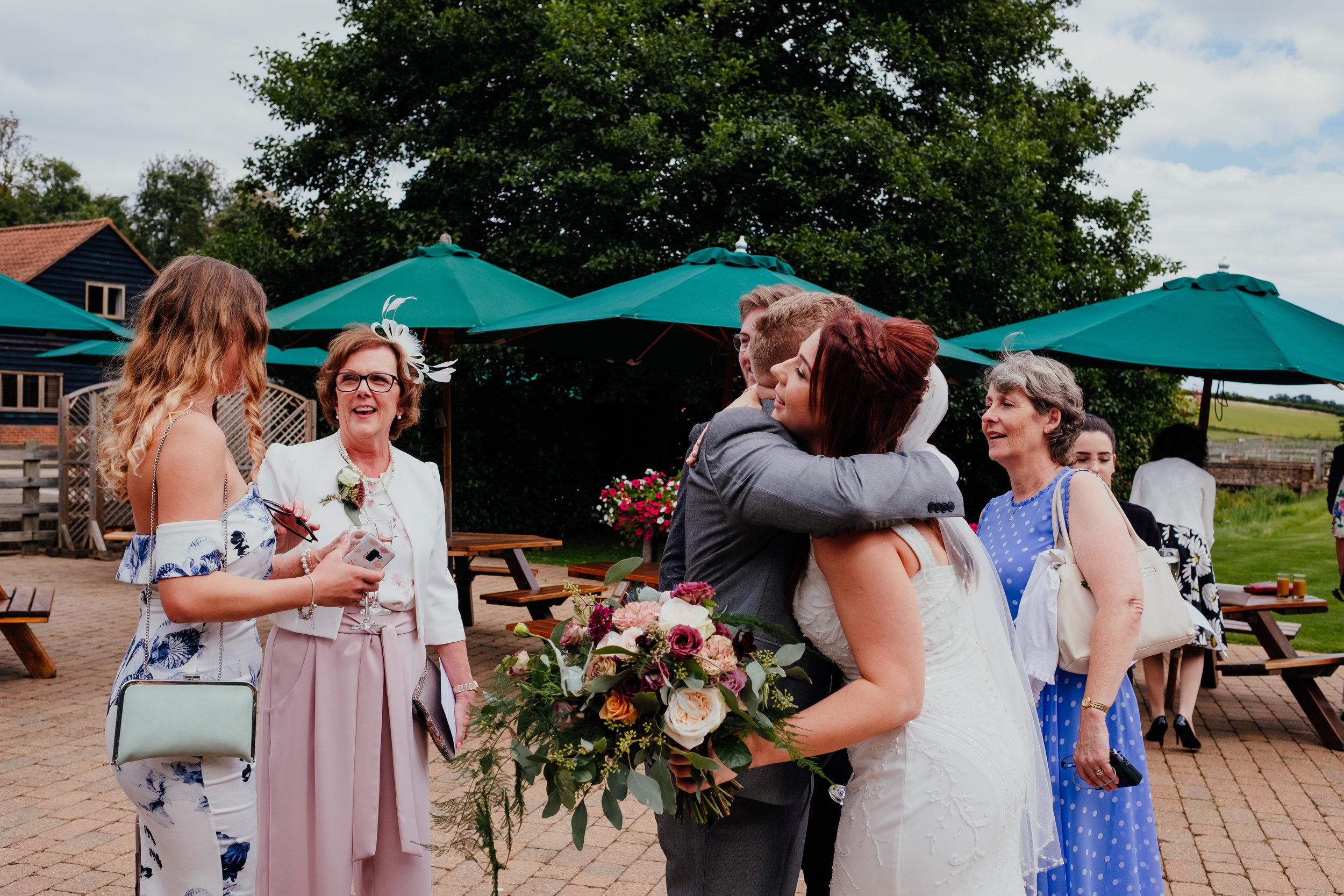 Bride hugs her brother after wedding ceremony