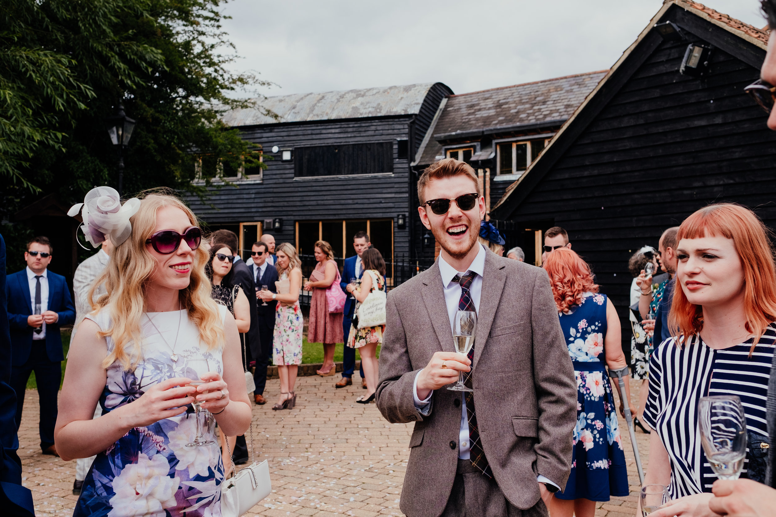 Wedding guests laughing at Tewin Bury Farm