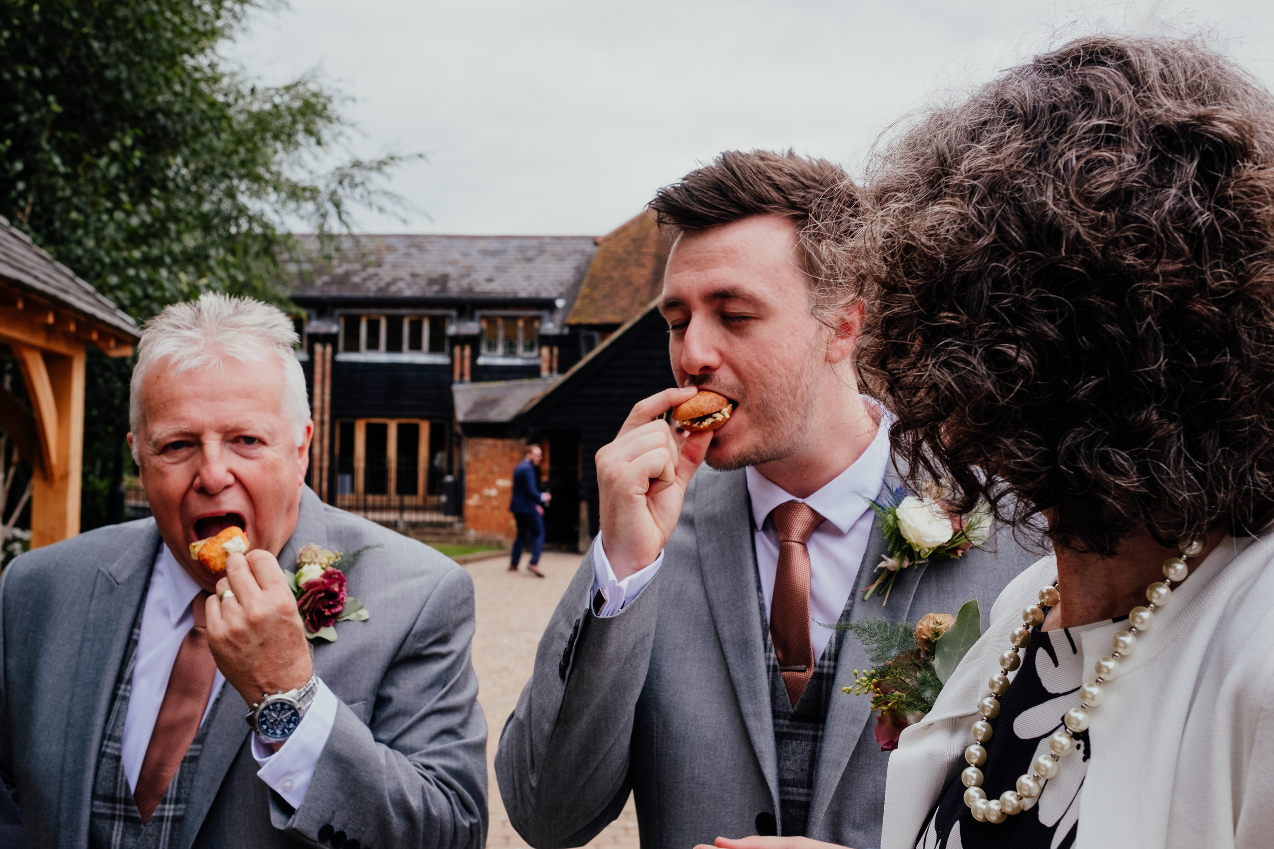 Groom and Father of the Bride eat canapés
