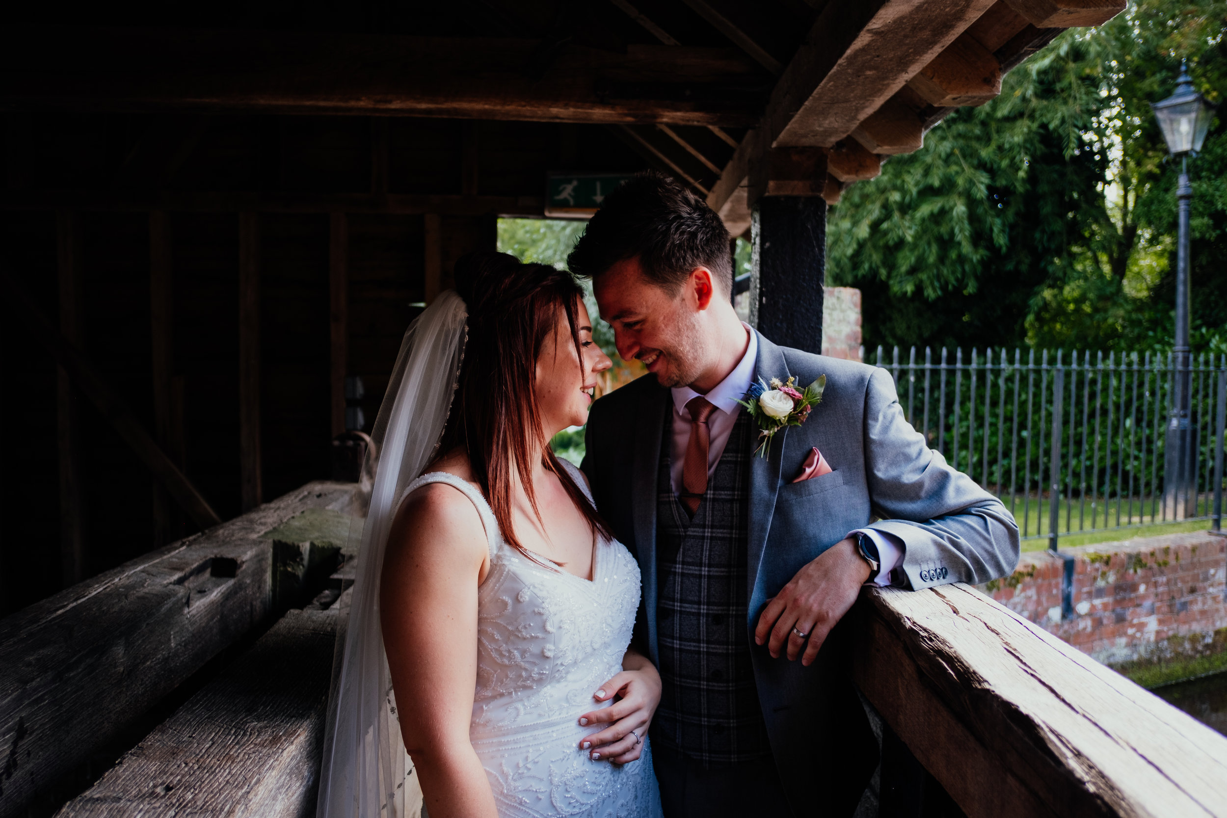 Newlywed couple smiling at each other on bridge at Tewin Bury Farm wedding