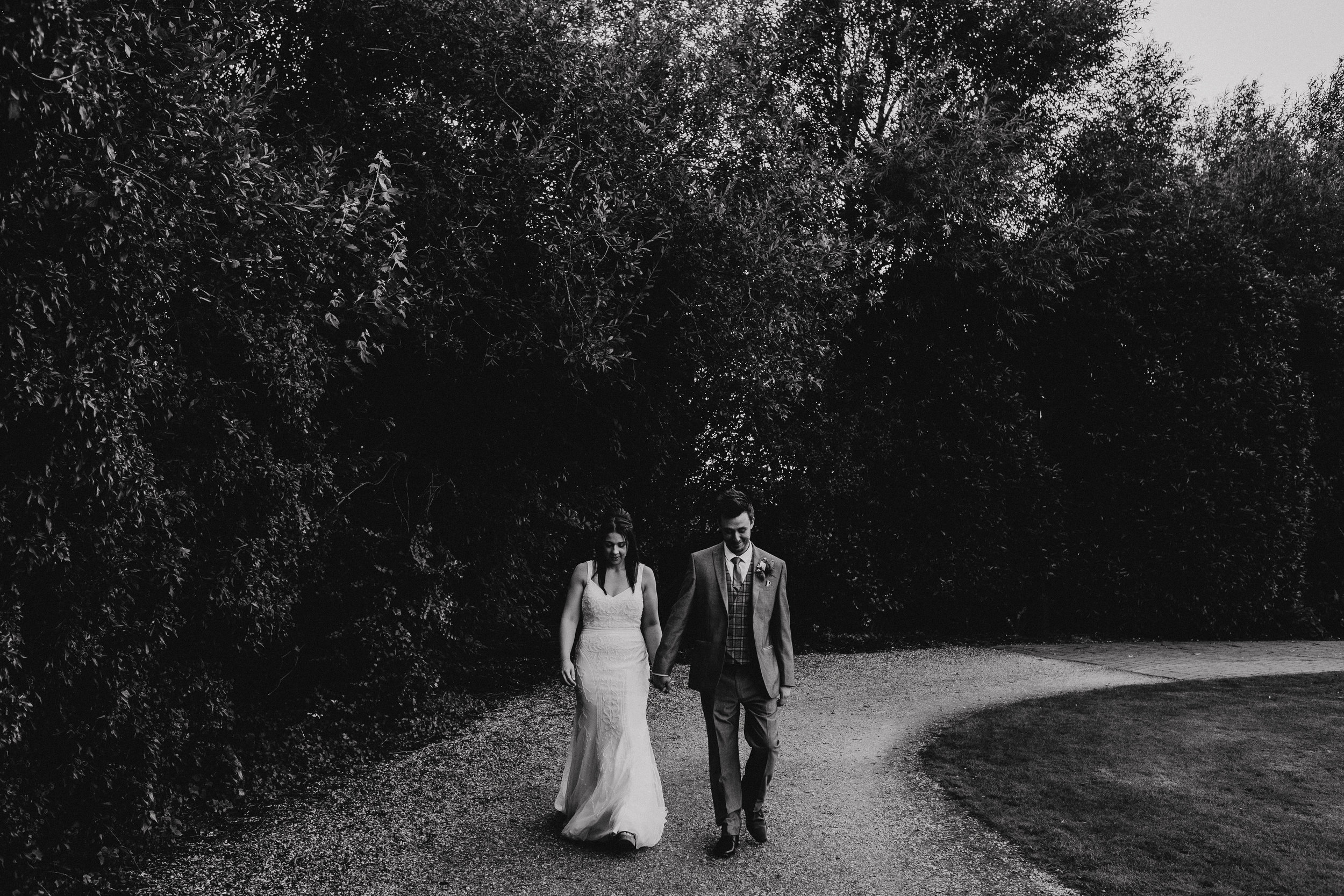 Bride and groom walking along at Tewin Bury Farm