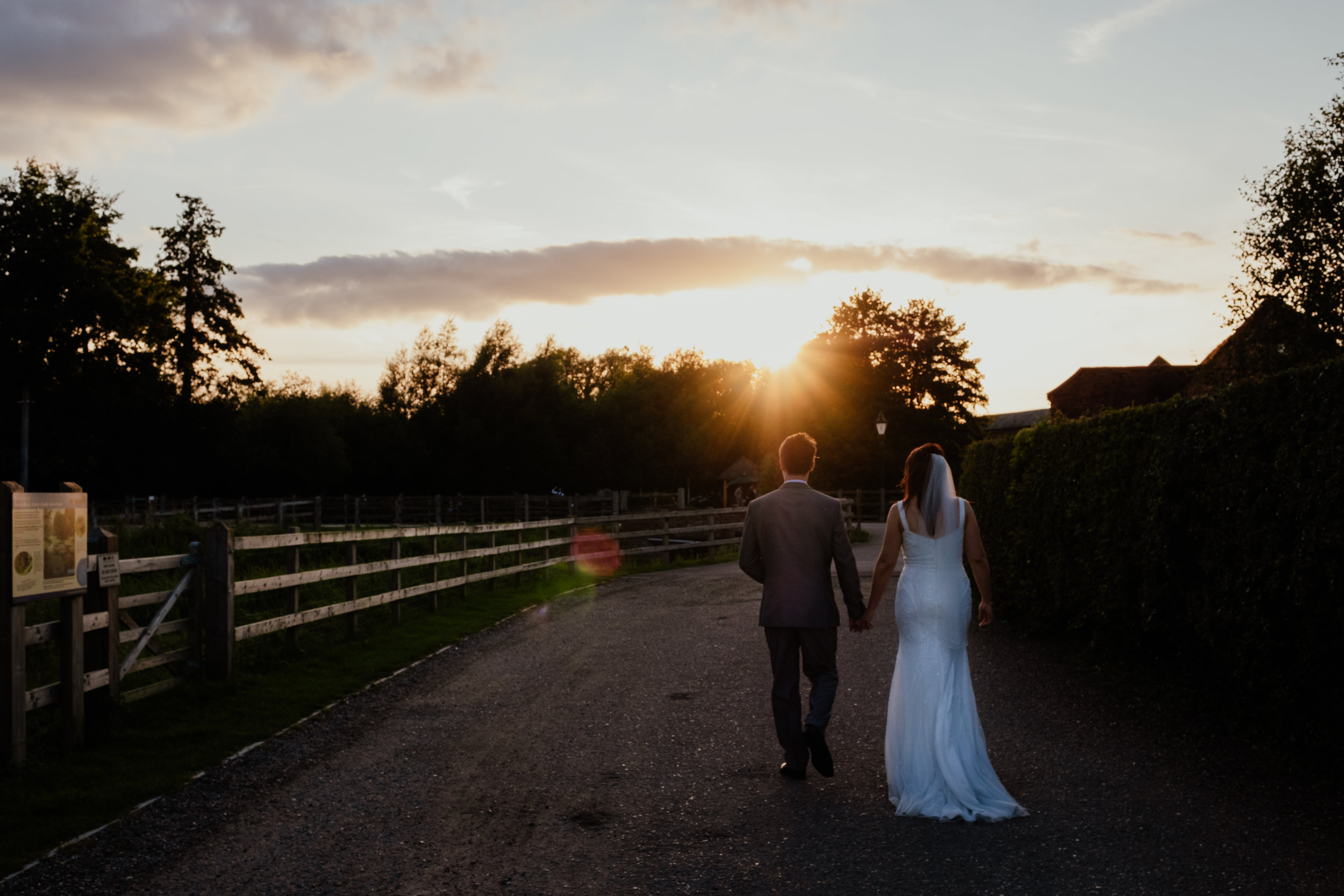 Bride and Groom walking towards the sunset at Tewin Bury Farm wedding