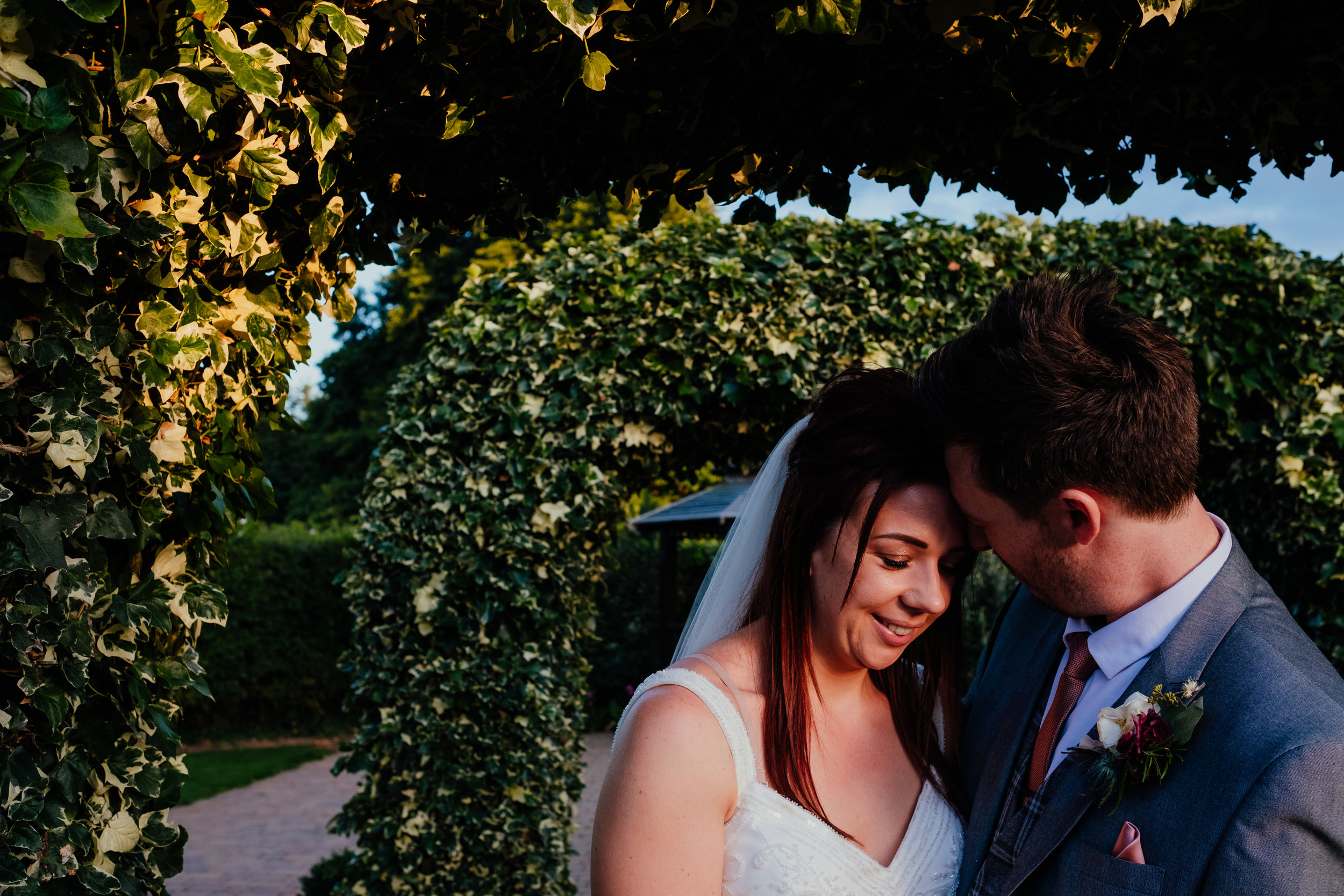 Bride and groom smiling at each other during sunset at Tewin Bury Farm wedding