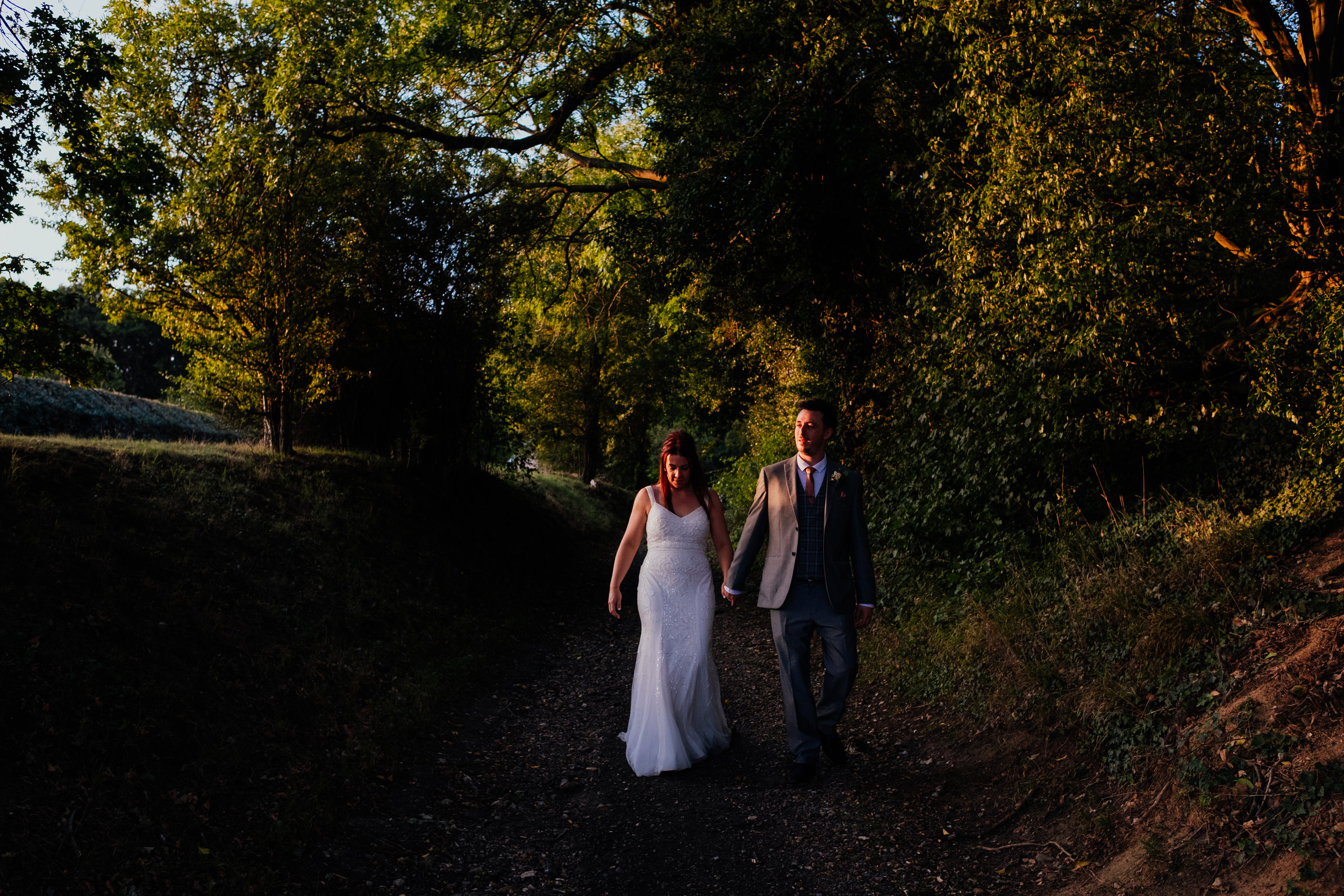 Bride and Groom walking in the sunset light during Tewin Bury Farm summer wedding