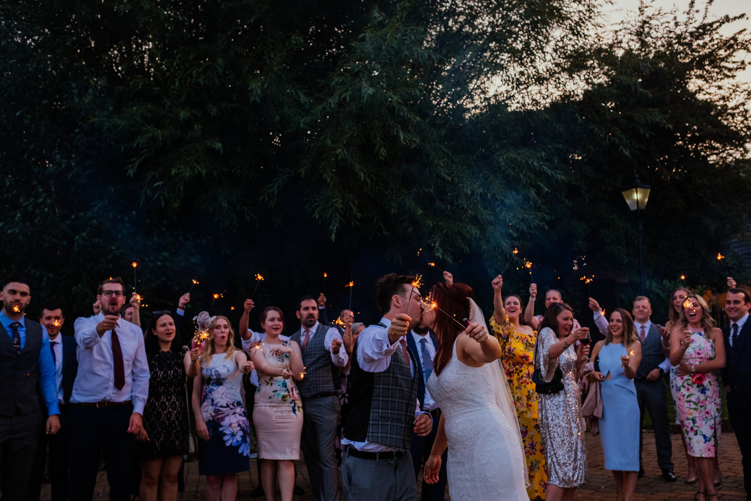 Bride and groom kiss during sparklers at Tewin Bury Farm wedding