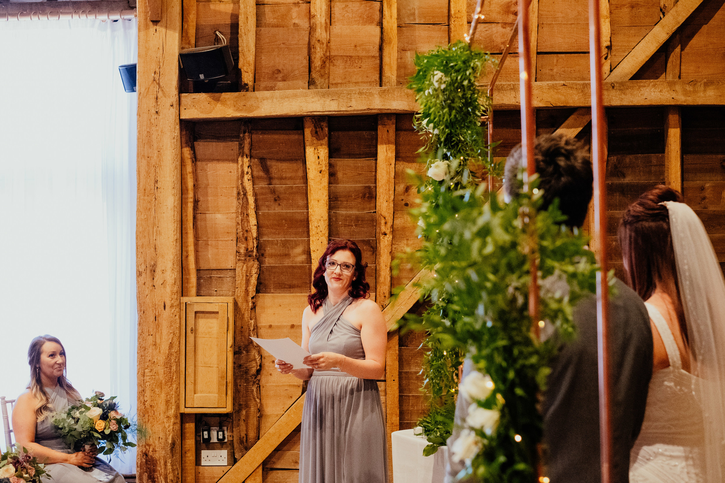 Bridesmaid and sister of the bride gives reading during wedding ceremony