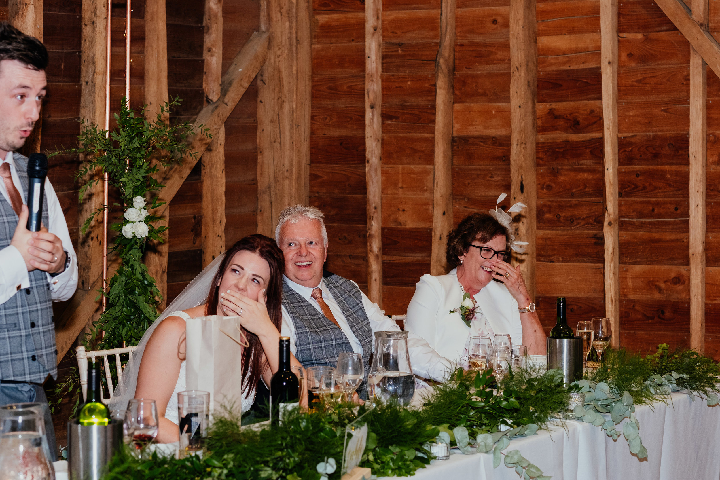 Bride and family laughing during groom's speech