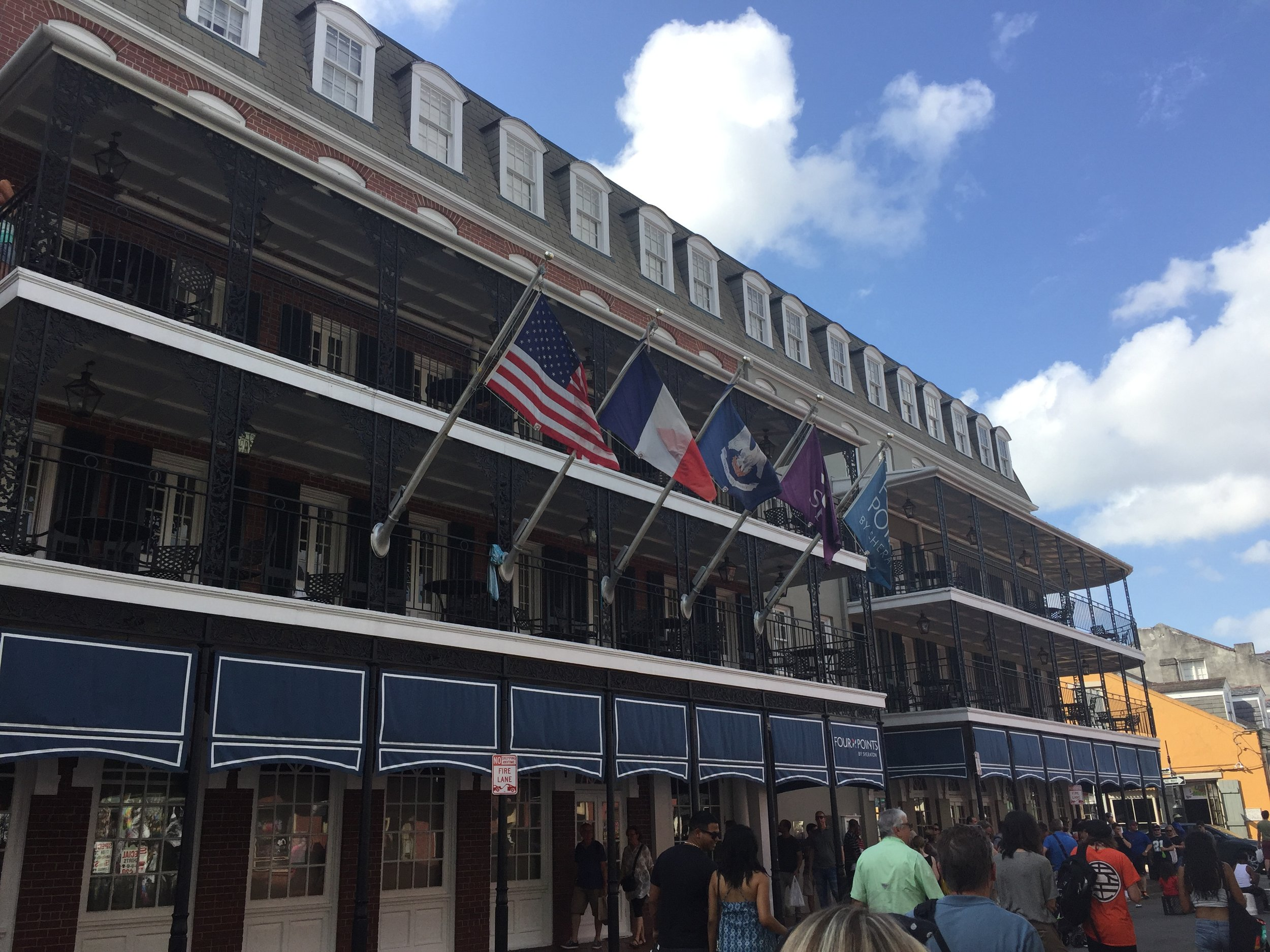 America, France, and Louisiana. All three flags displayed together on the famous Bourbon St. outside of a nice hotel.