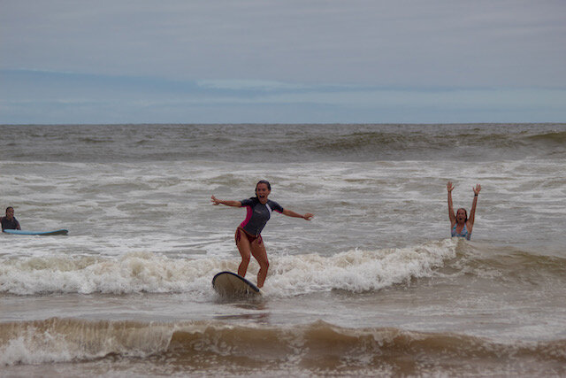 (Left: Karen Slattery, happily atop her first wave. Right: Proud teacher Rachel Sandquist pumping her fists)