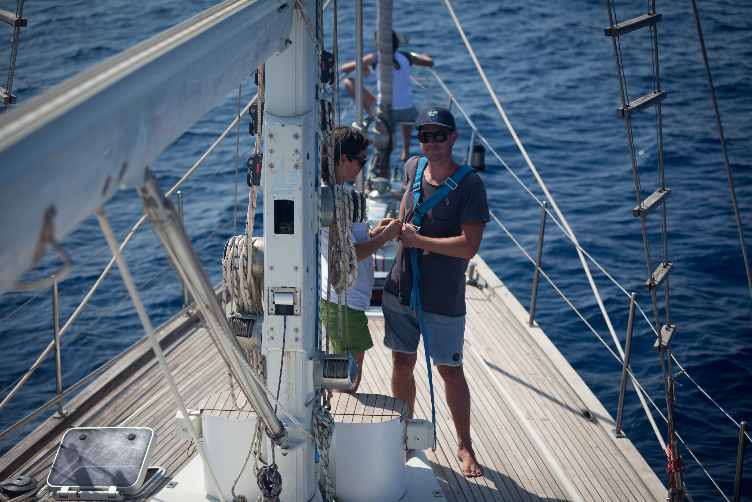 Tethy's Principal Field Investigator, Alessia Scuderi, straps up Co-Director, James Sherwood, so he can climb up the mast and look out for fin whales.