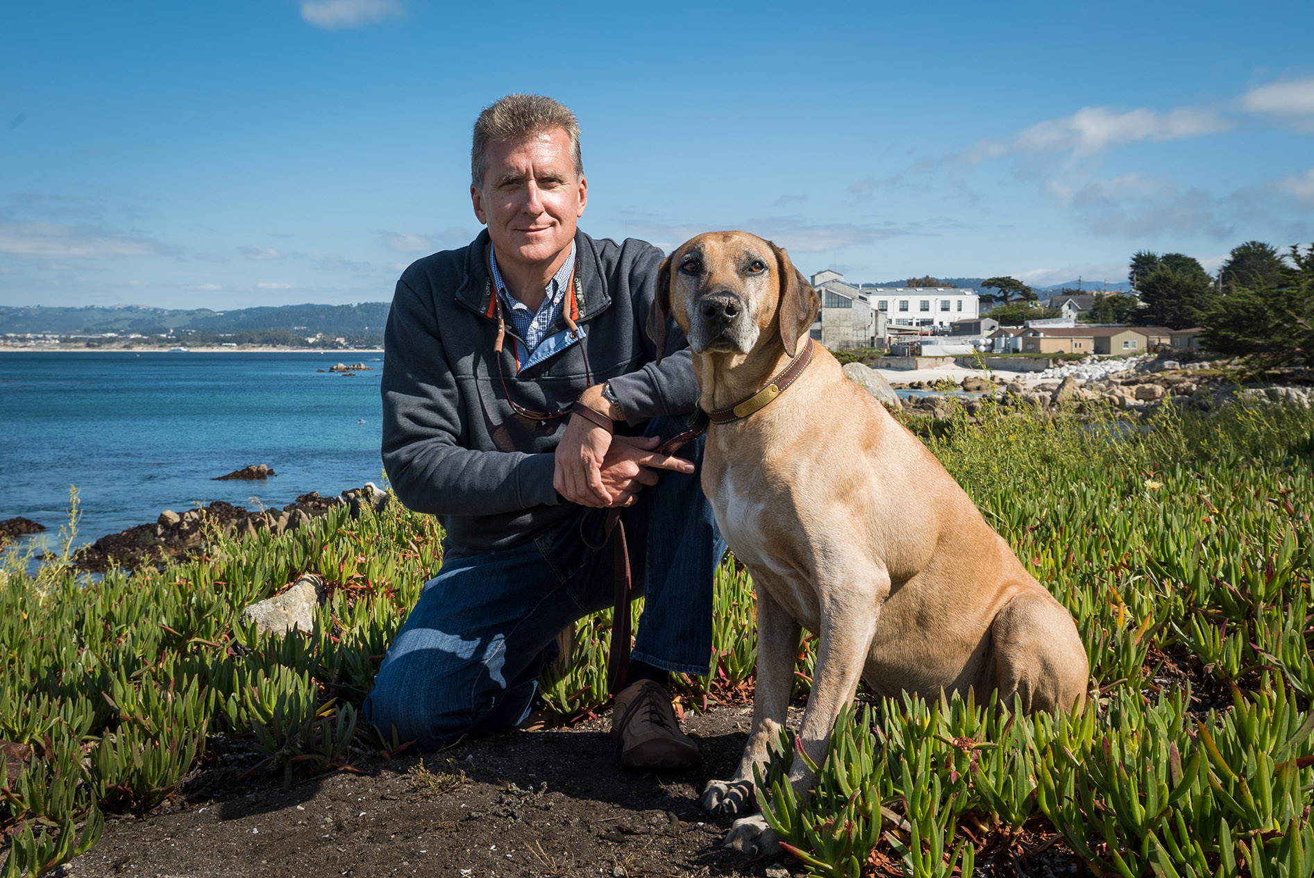 Mike and his ridgeback. Behind Mike is the marine sanctuary and Monterey Bay Aquarium where he worked as Vice President between 2004-12.