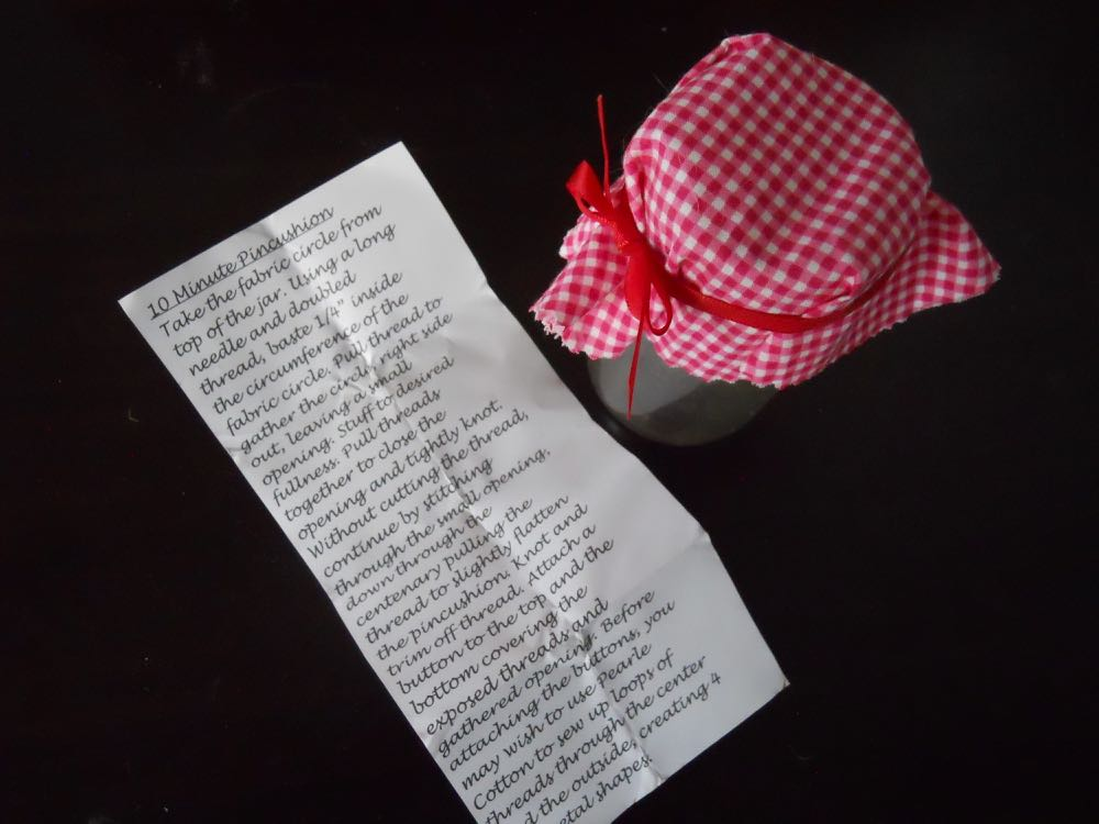 Instructions to tuck under the fabric top of a food jar on how to make the jar into a pincushion.