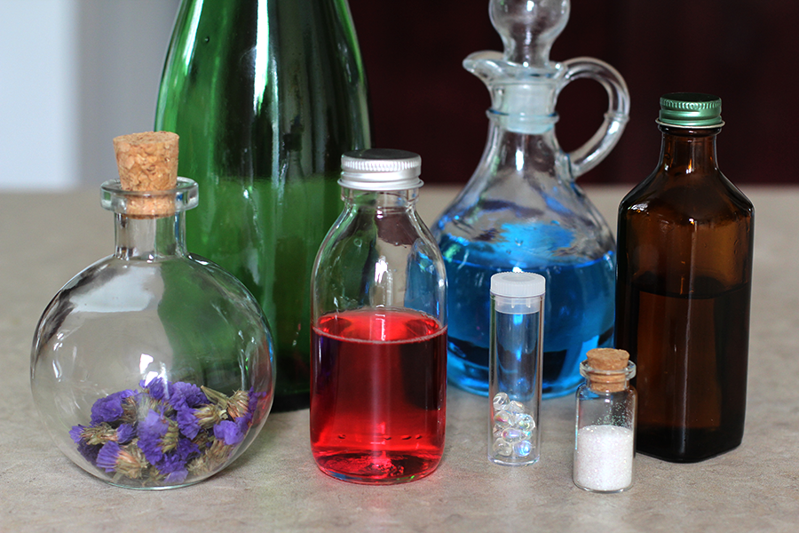 Add colored water, glitter, jewels and dried flowers to bottles.