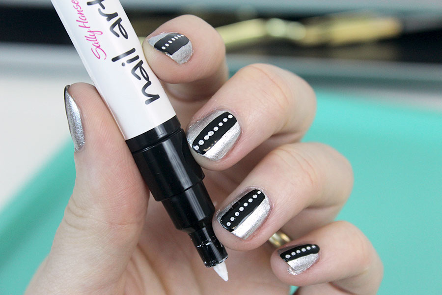 Paint little dots on the thick black line using a white nail art pen.