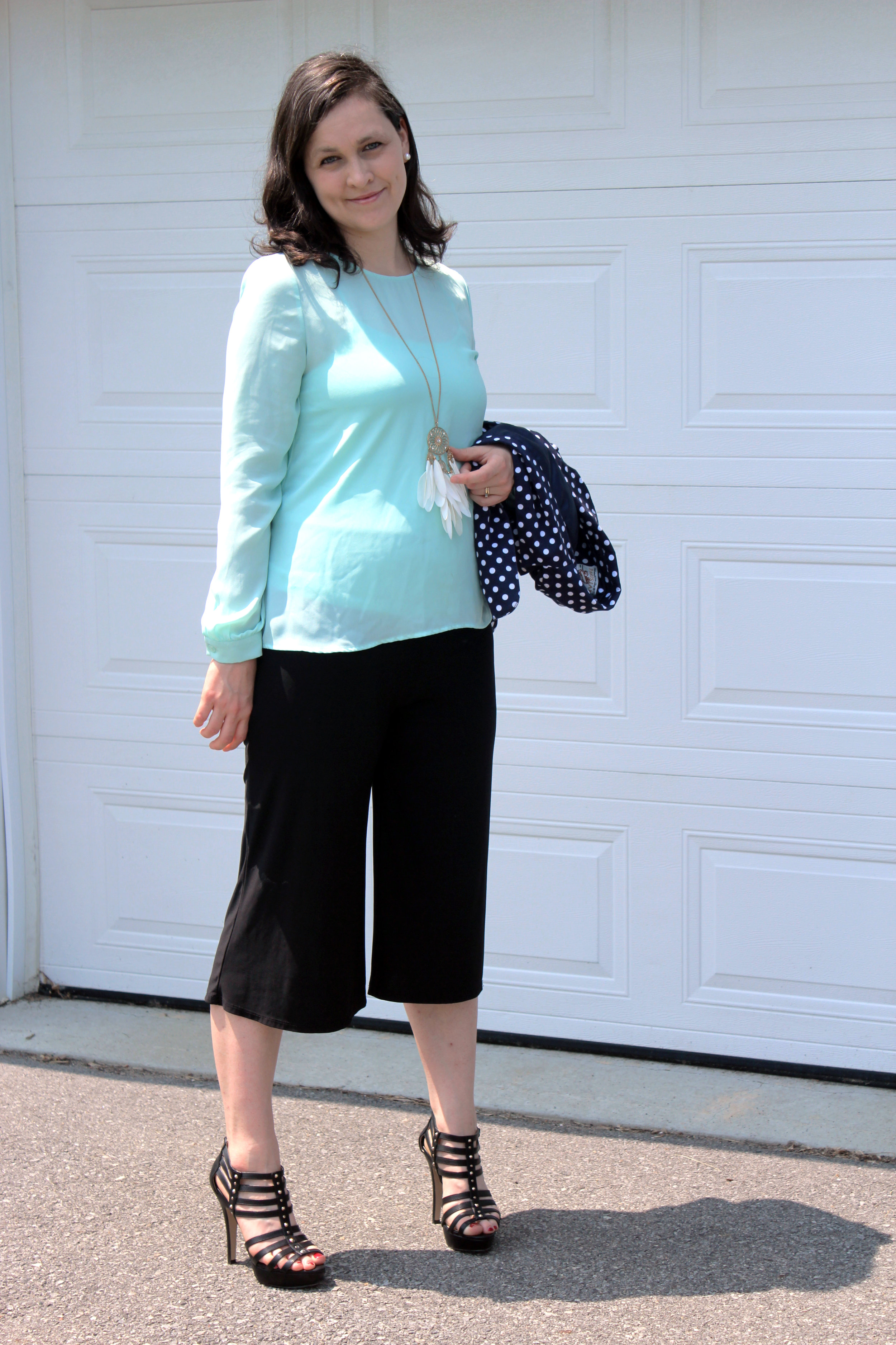 turquoise blouse navy blue polka dot jacket black pants standing up.jpg