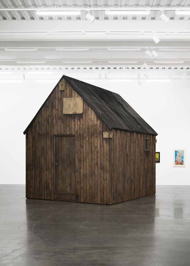 Robert Kusmirowski,  Unacabine,  2008. Wooden boards, tar paper, plywood, tin pipe, oil, acrylic. 398 x 322 x 355 cm. Courtesy of Foksal Gallery Foundation, Warszawa and New Museum, New York. Photo by Benoit Pailley.