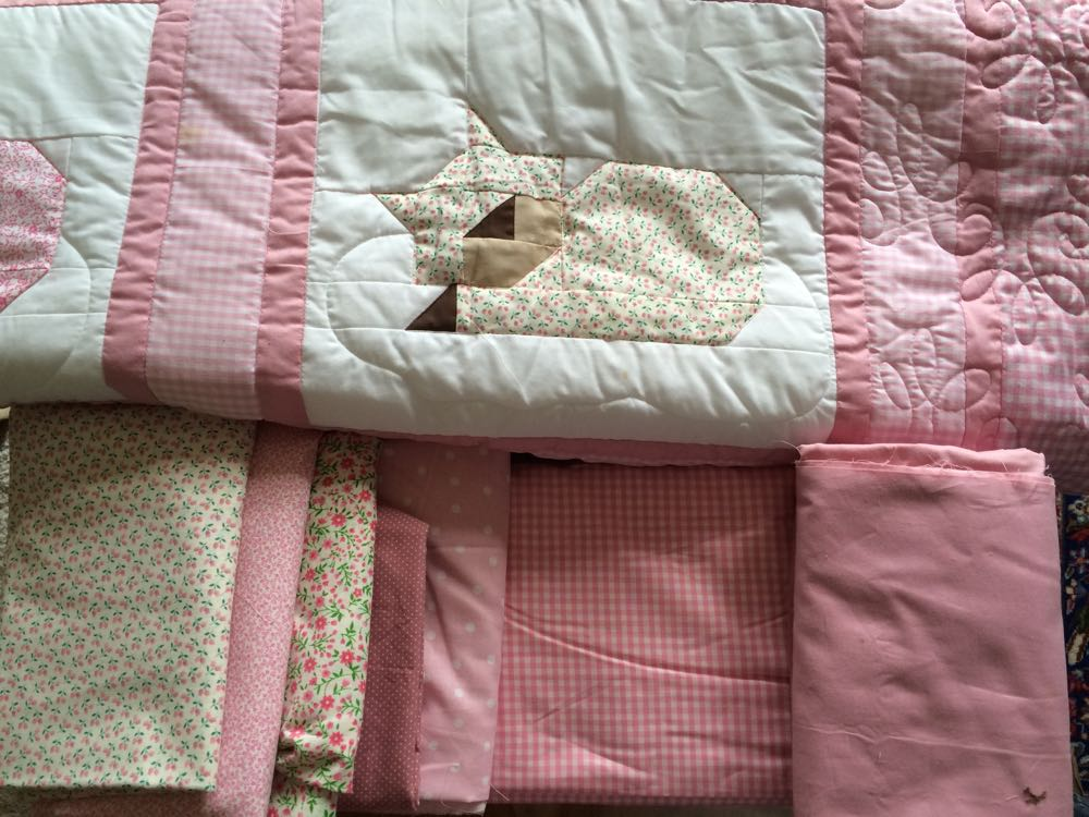 Choosing fabrics for a custom sleeping cats quilt in pinks.