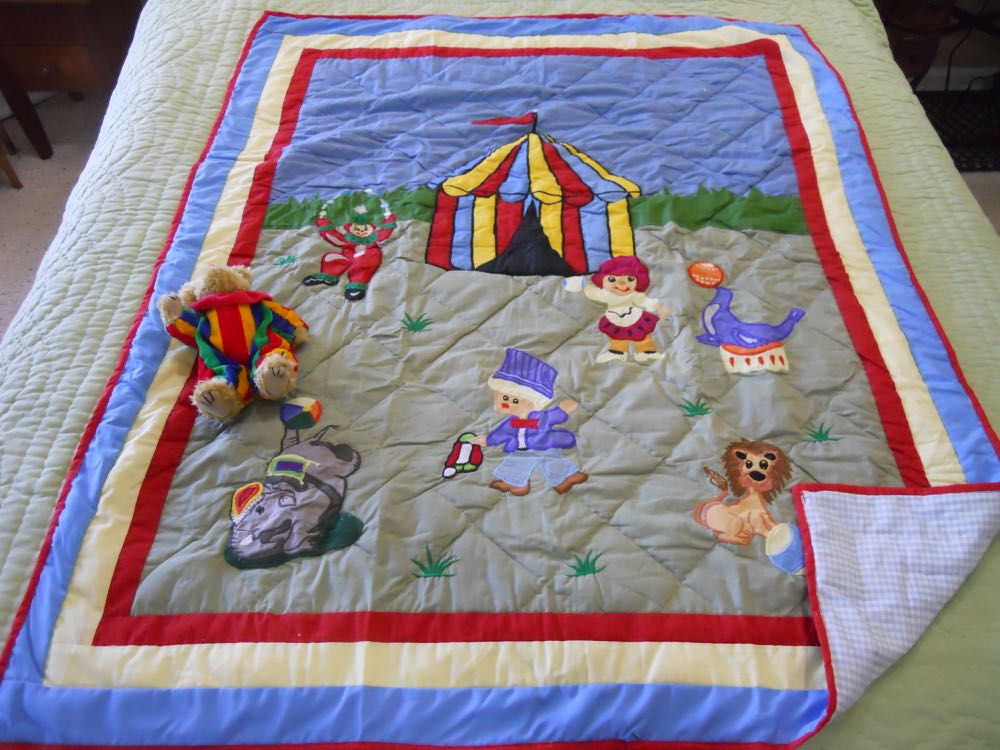 Circus Baby Crib Quilt Gift Set includes a bear toy dressed in a cute clown suit.