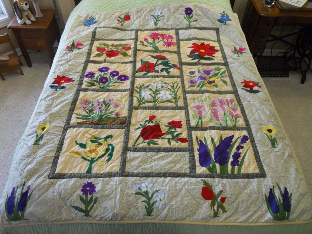 Detailed applique and embroidery are so pretty in this Wildflowers Lap Quilt Wall Hanging.