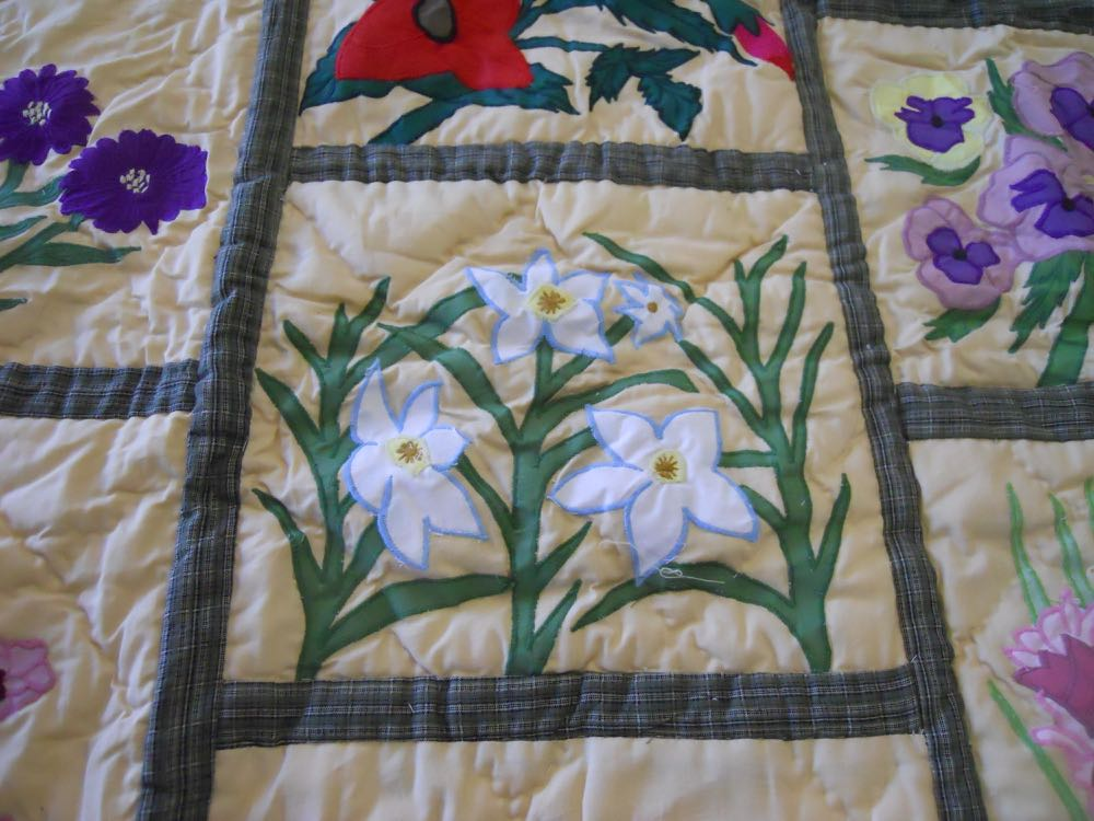 Applique embroidered wildflowers on this lap quilt throw wall hanging are very detailed.