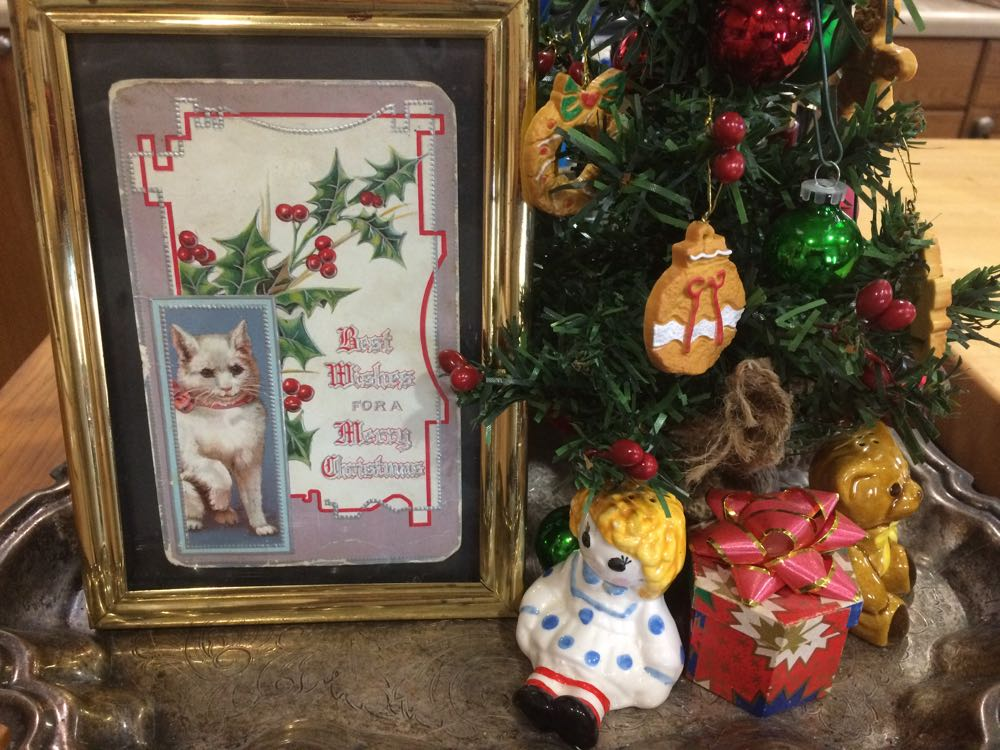 A vintage Christmas postcard joins a small decorated tree and presents in my kitchen.