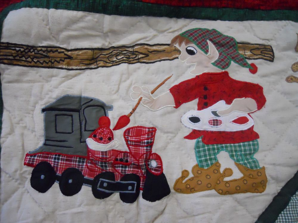 This applique elf in santa's workshop quilt throw wall hanging looks like he's almost finished.
