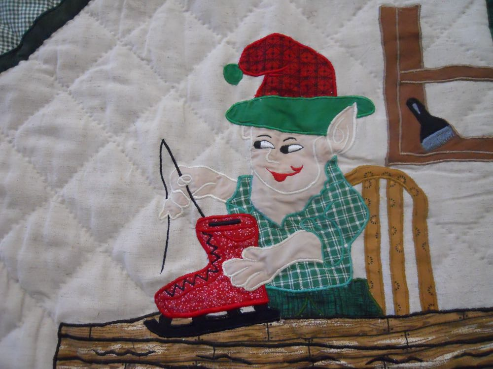 This elf is lacing a set of skates in santa's workshop quilt throw all hanging. Love his smile!