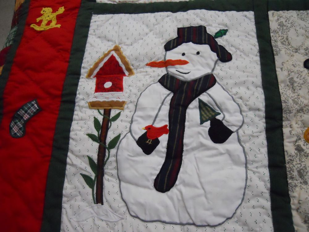 A snowman keeps a red cardinal company in this traditional Christmas snow scene.