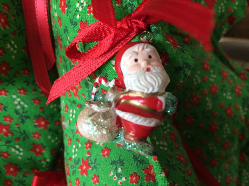 Little Santa Claus with bag of gifts ornaments on fabric Christmas tree.
