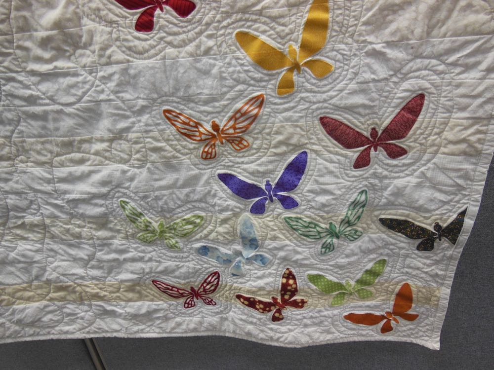 Different fabrics form the applique butterflies in this personalized gift.