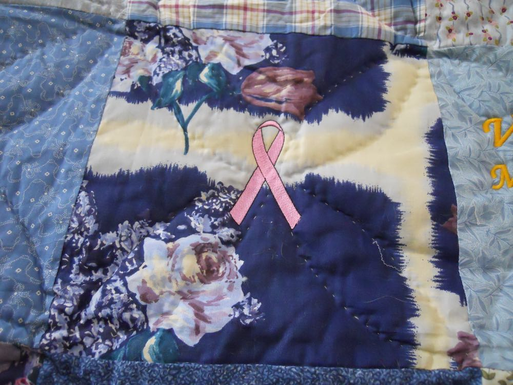 Custom embroidered breast cancer ribbon as part of this personalized handmade quilt throw.