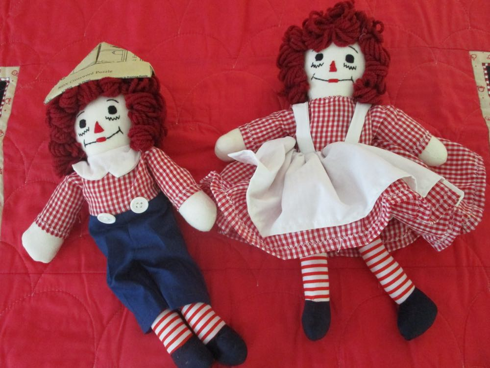Two 12-inch handmade rag dolls compliment the handmade baby crib quilt.