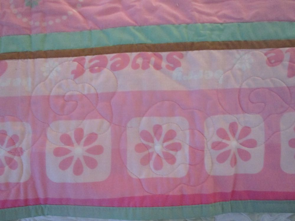 Detailed machine quilting makes this baby crib quilt easy to wash and dry.