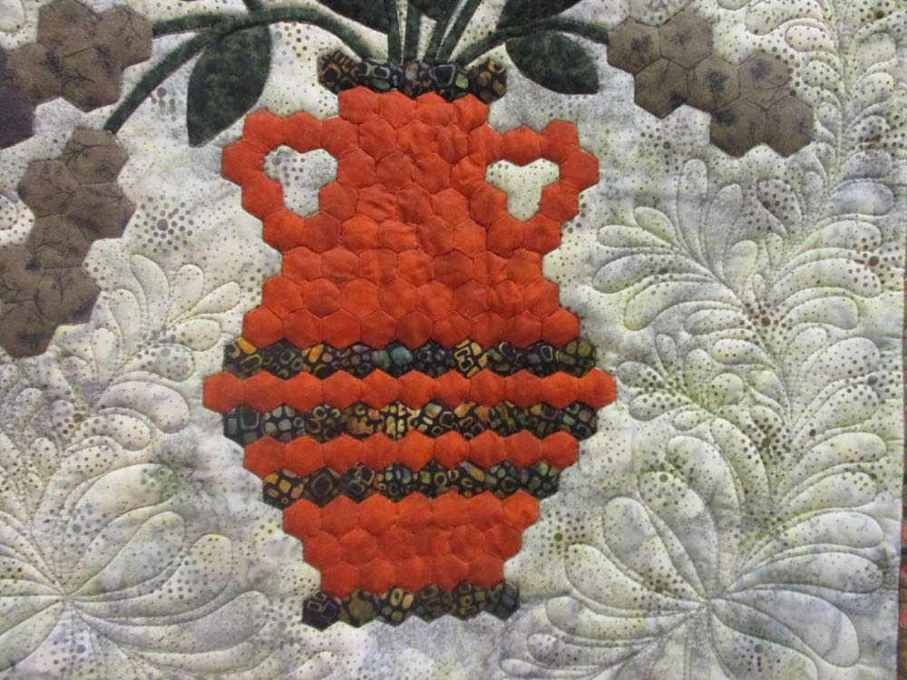 Look at the detail work in the orange vase that holds the cattails and chrysanthemums.