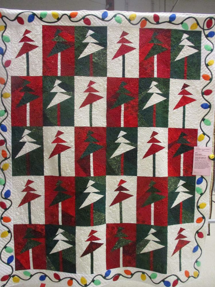 Modern patchwork Christmas trees get a little help from a border string of lights.