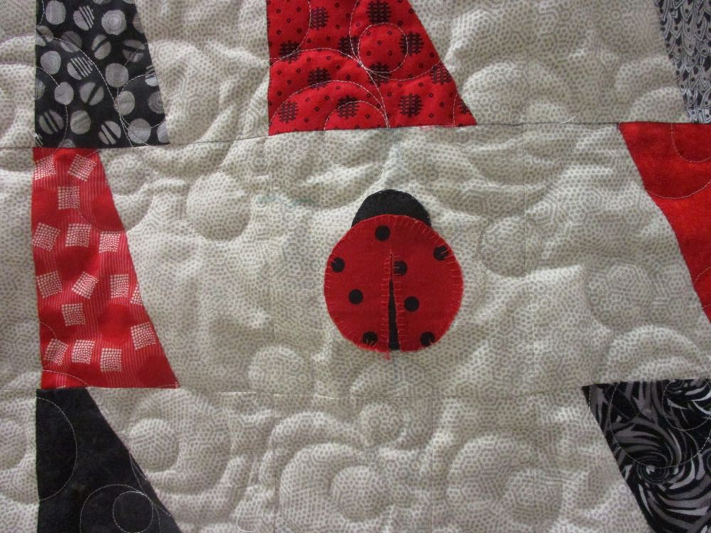 Here is a closer look at the center red ladybug and the surrounding quilting.