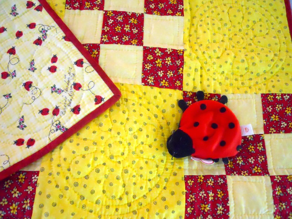 A ladybug toy was added to this ninepatch ladybug baby quilt. (Photo by Charlotte Ekker Wiggins)