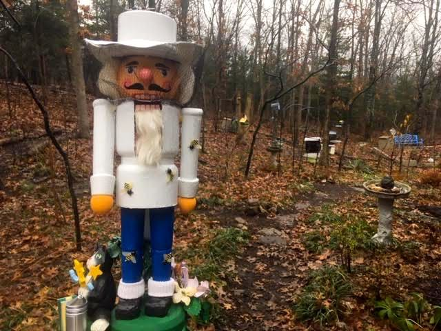 The finished beekeeper nutcracker with bee hives in the background. (Photo by Charlotte Ekker Wiggins)