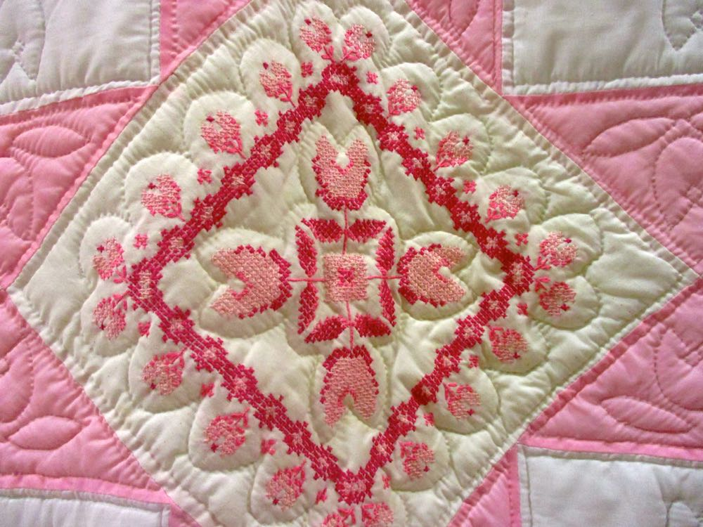 Very detailed embroidery makes up Pink Cross Stitch Quilt blocks. (Photo by Charlotte Ekker Wiggins)