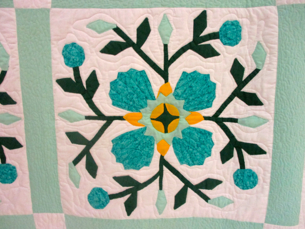 Unusual colors for a rose quilt, aquamarine fabrics against white. (Photo by Charlotte Ekker Wiggins)