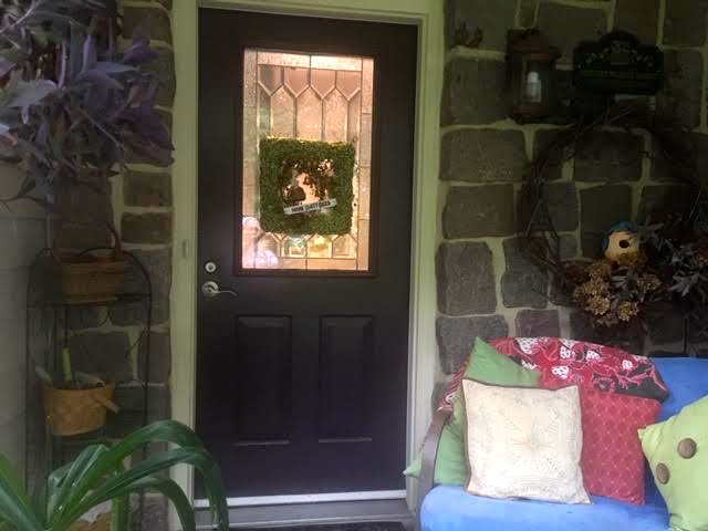"My ""new"" square green door wreath fits in nicely on my front deck. (Photo by Charlotte Ekker Wiggins)"