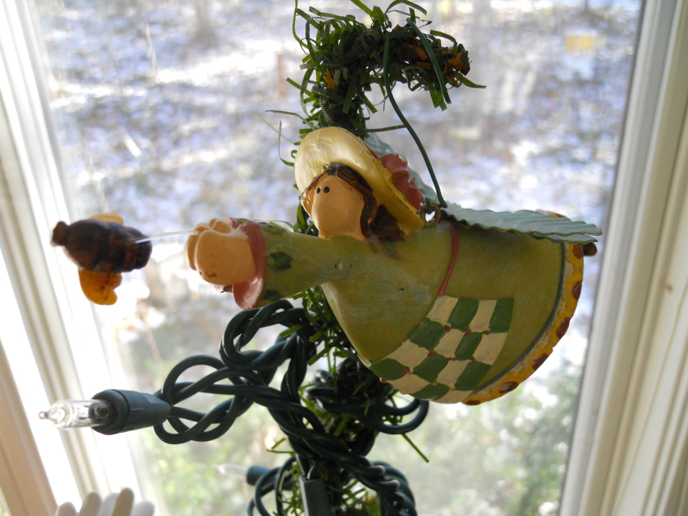 Charming flying angel chasing a bee is my Christmas tree topper this year.