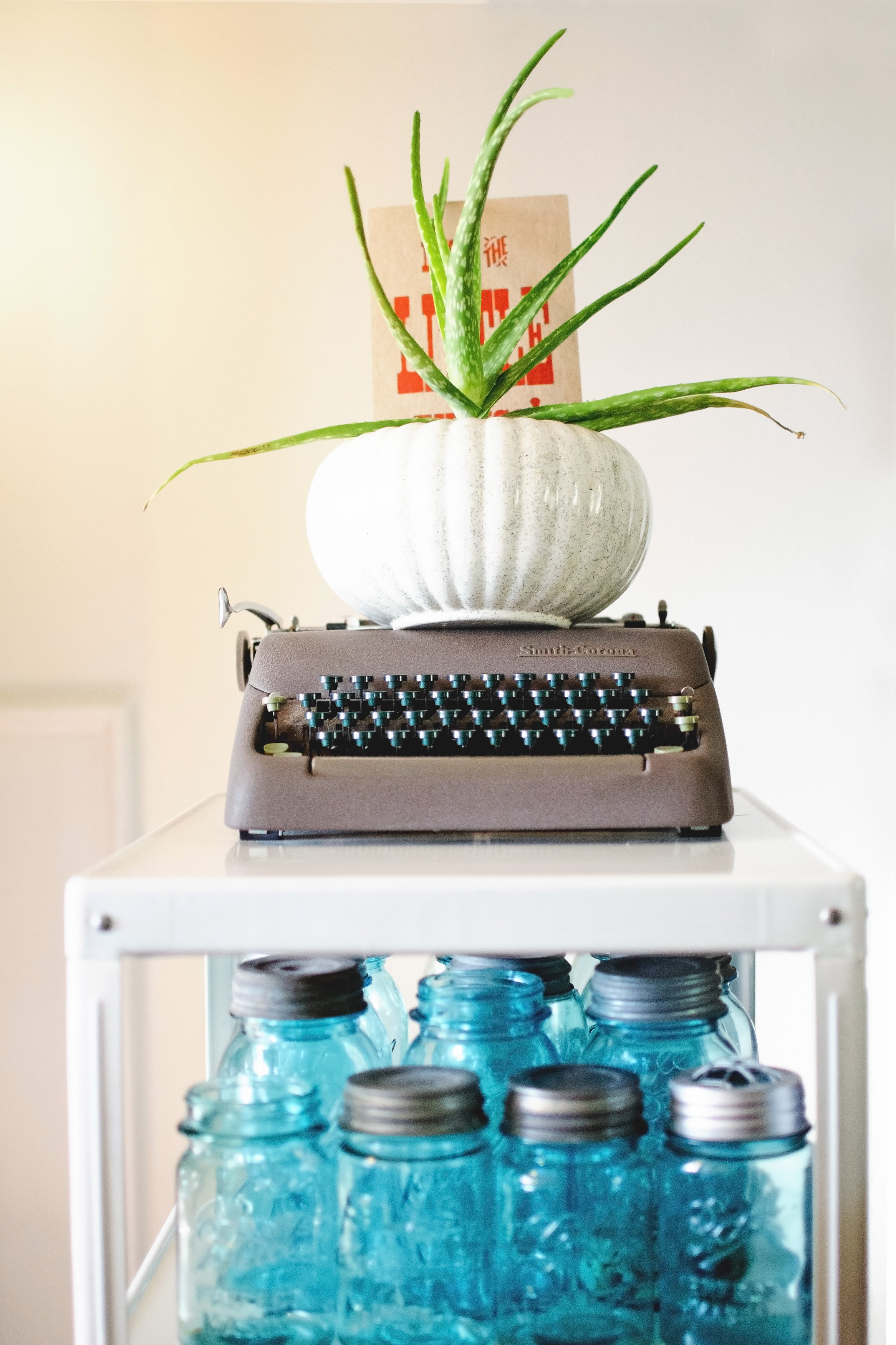 White metal shelving with blue ball jars, a vintage typewriter, and potted plant. H.Prall & Co. | hprallandco.com