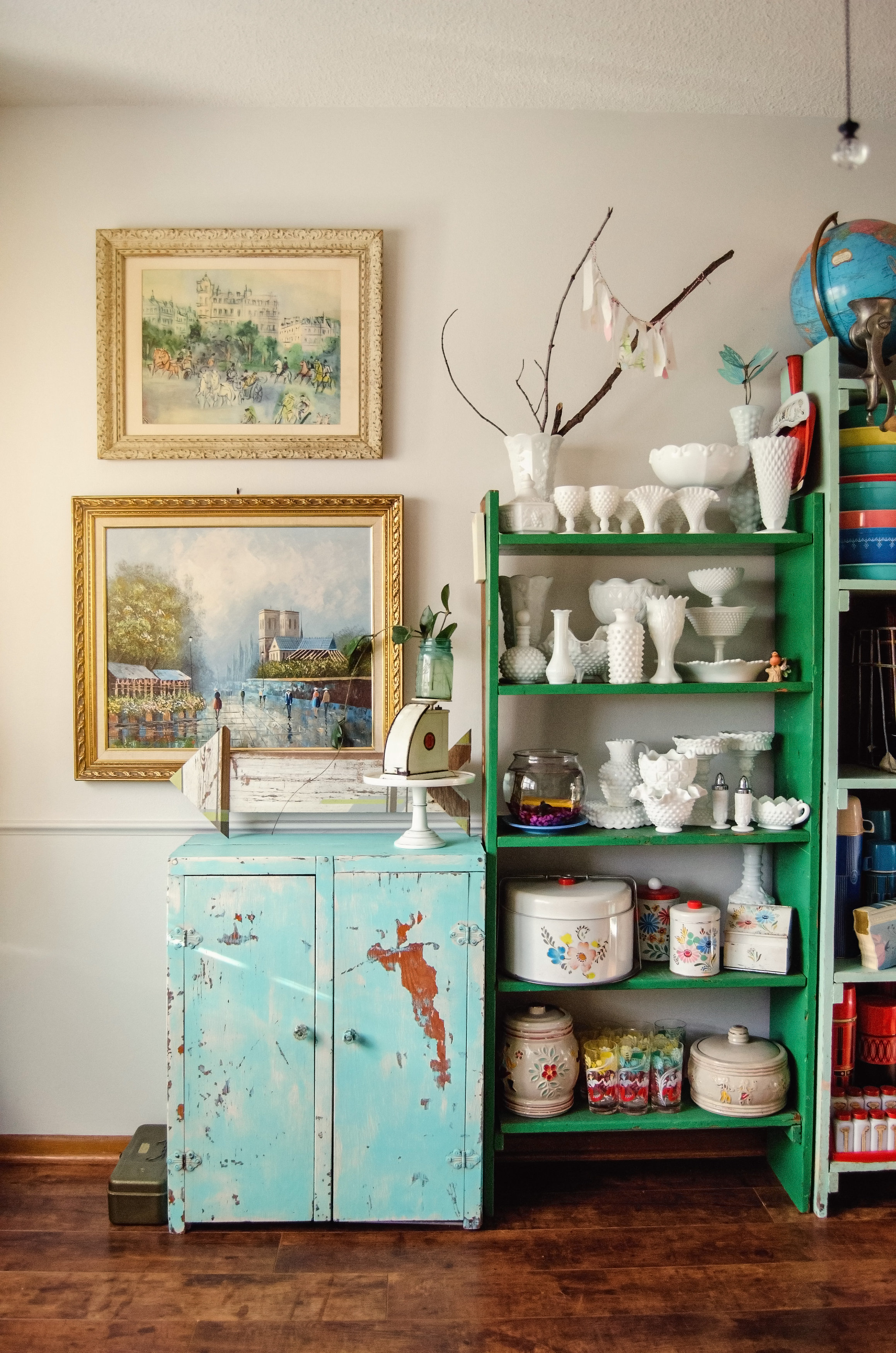 A chippy aqua cabinet next to kelly green shelving holding vintage milk glass. H.Prall & Co. | hprallandco.com