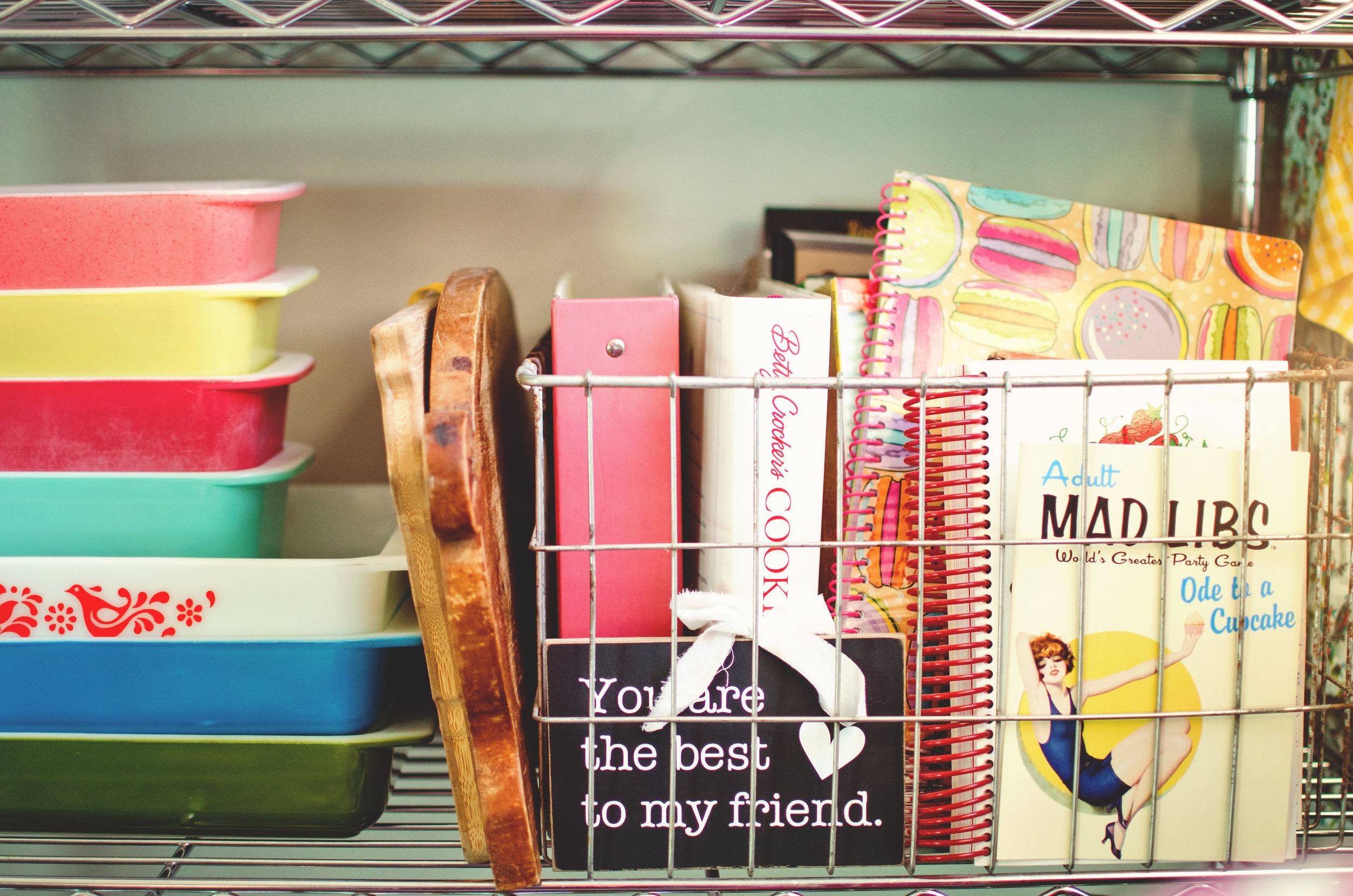 Wire basket of recipe books next to a stack of colorful vintage Pyrex. H.Prall & Co. | hprallandco.com
