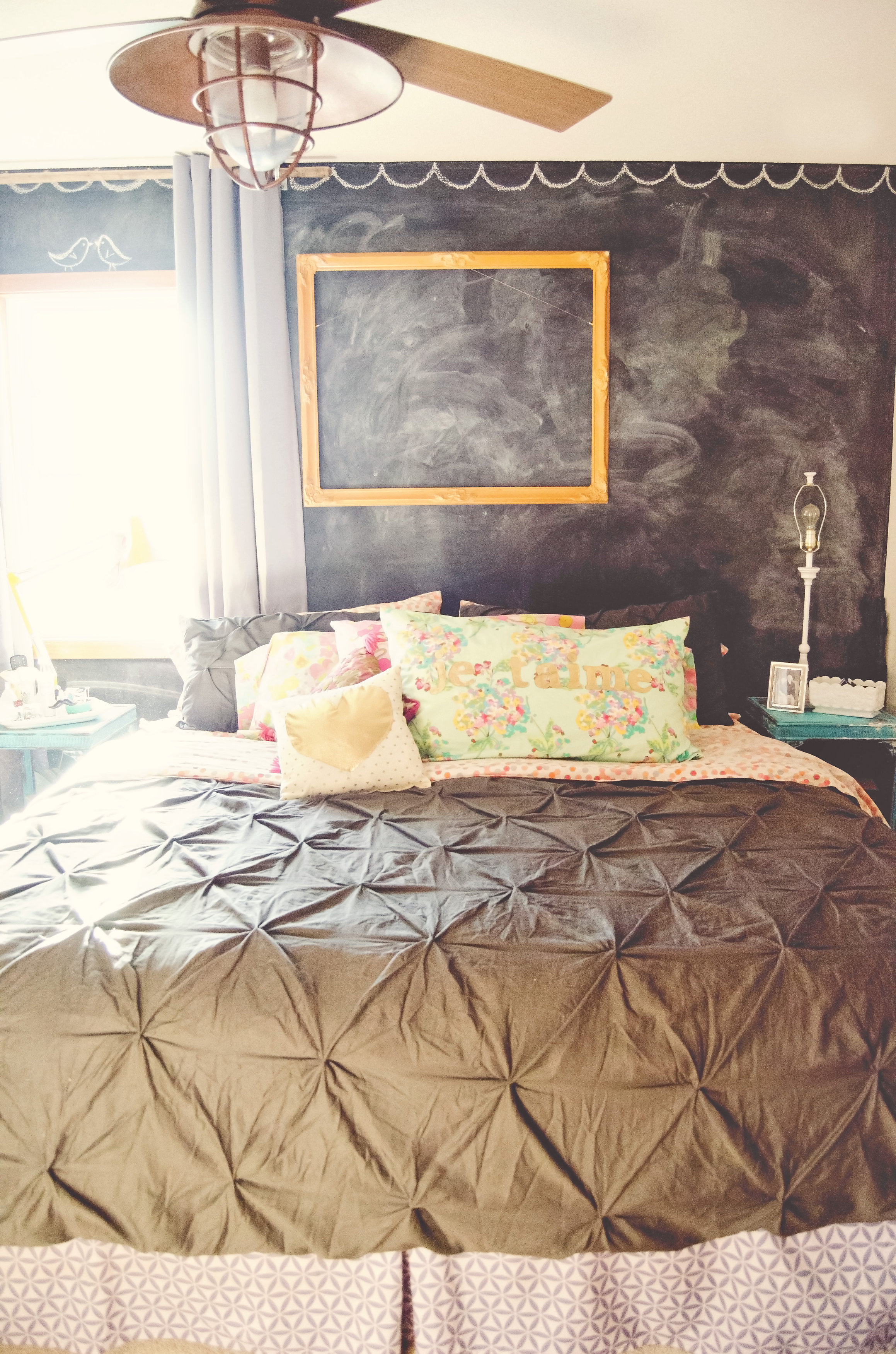 Chalkboard wall as a headboard with an empty yellow frame. | hprallandco.com