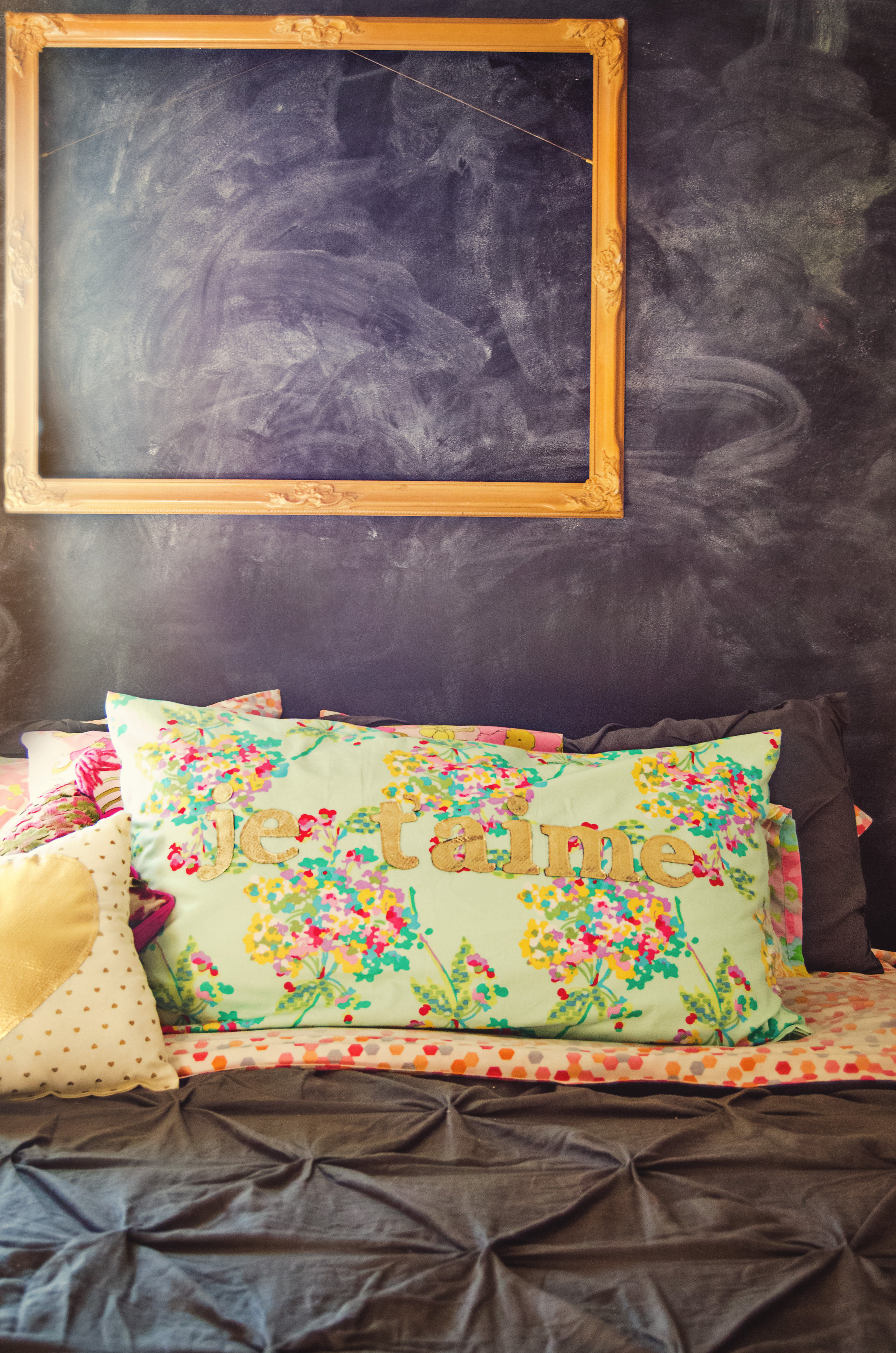 Chalkboard wall behind the bed with a gold frame. | hprallandco.com