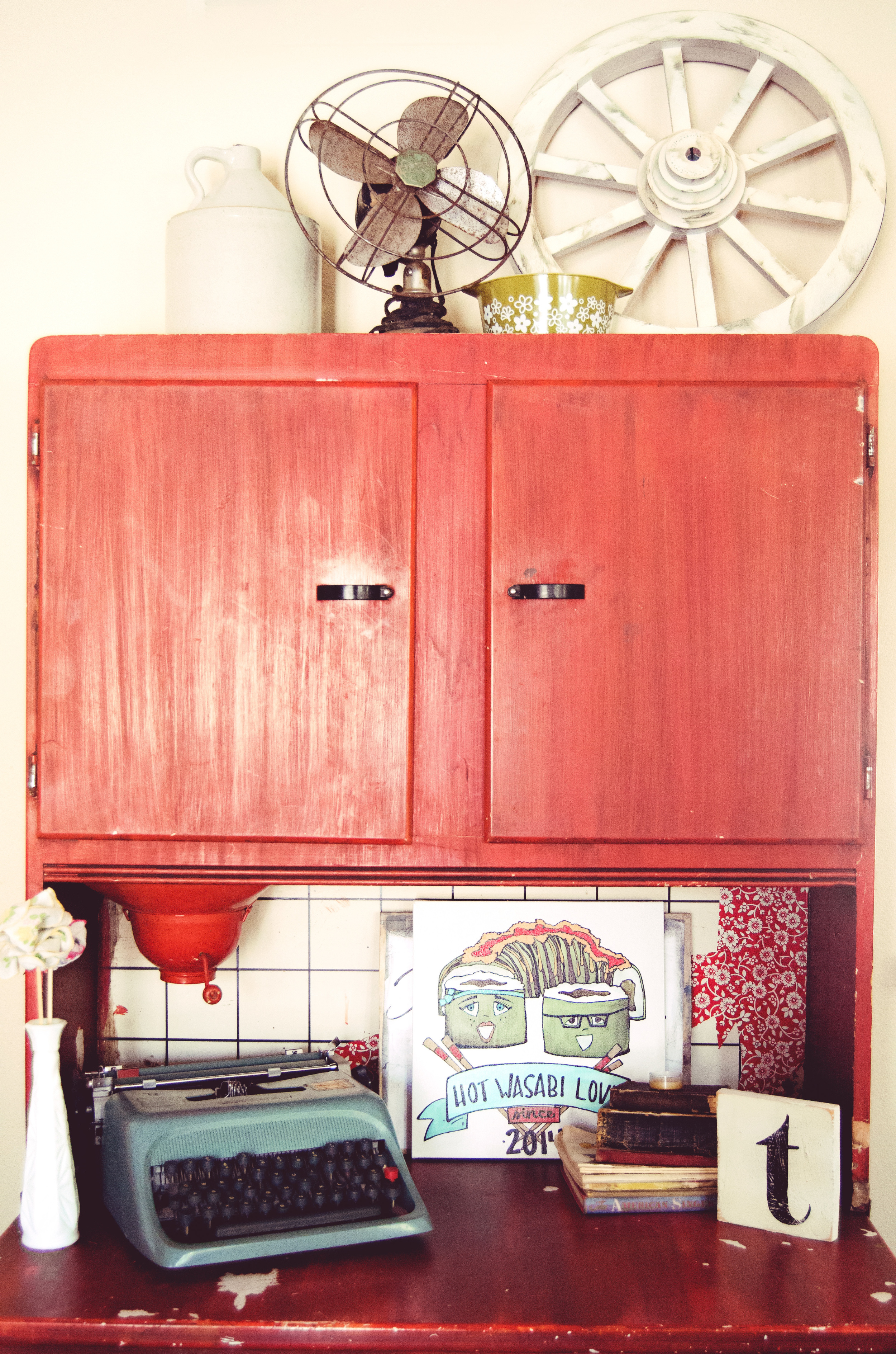Red cabinet styled with a vintage typewriter, vintage fan, and other vintage treasures. | hprallandco.com