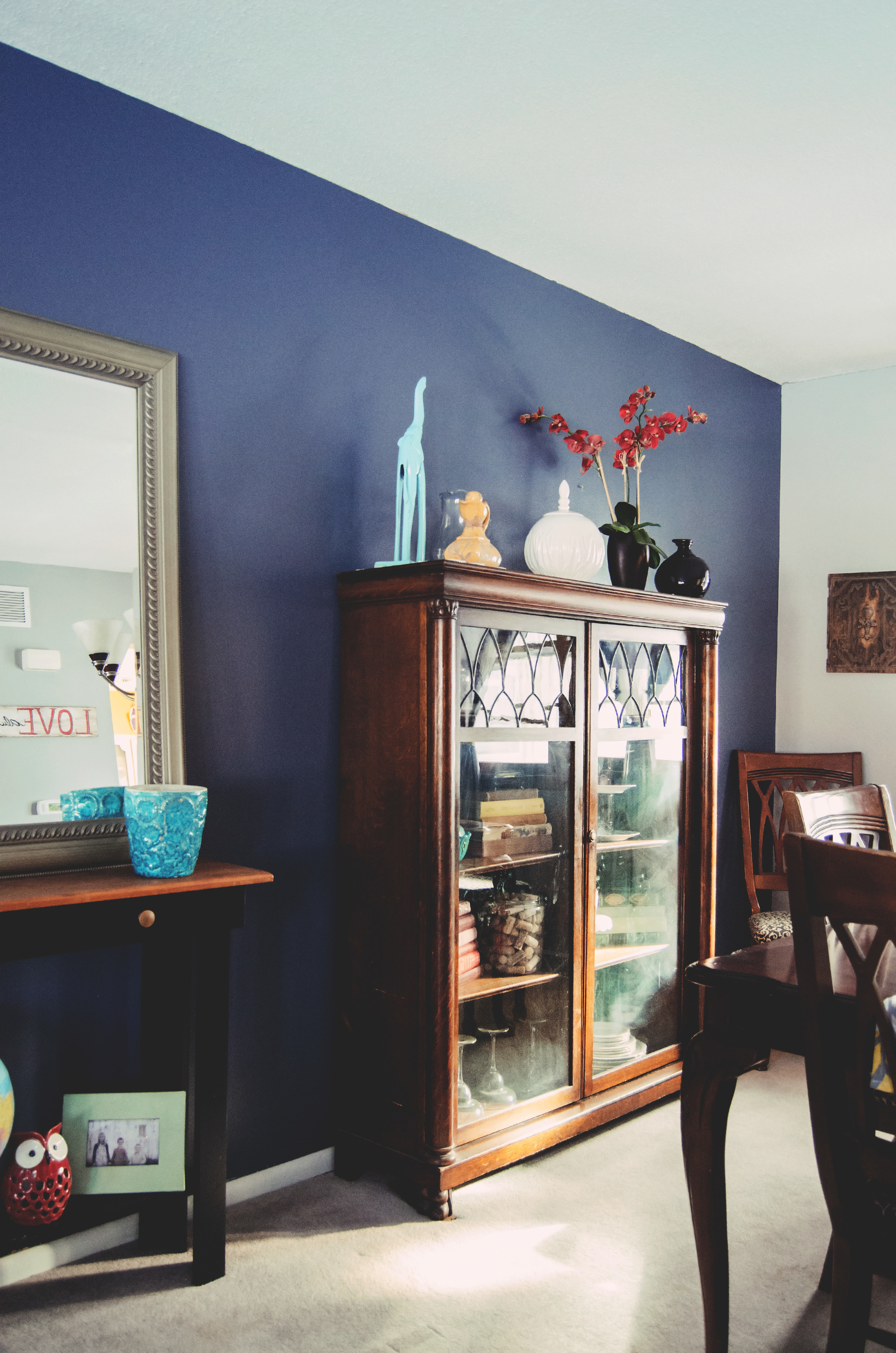Blue dining room accented with beautiful wood pieces, and small pops of color. | hprallandco.com