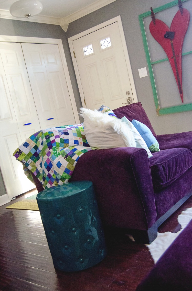 Purple loveseat with a bright quilt and teal garden stool as an endtable. || RustopiaConsulting.com